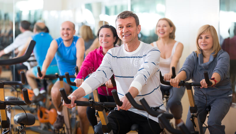 Man on fitness cycle in fitness club. Elderly men on fitness cycle in fitness club royalty free stock photo