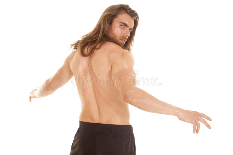 Man fitness no shirt arms out back looking. A man in his fitness clothes looking over his shoulder royalty free stock photos