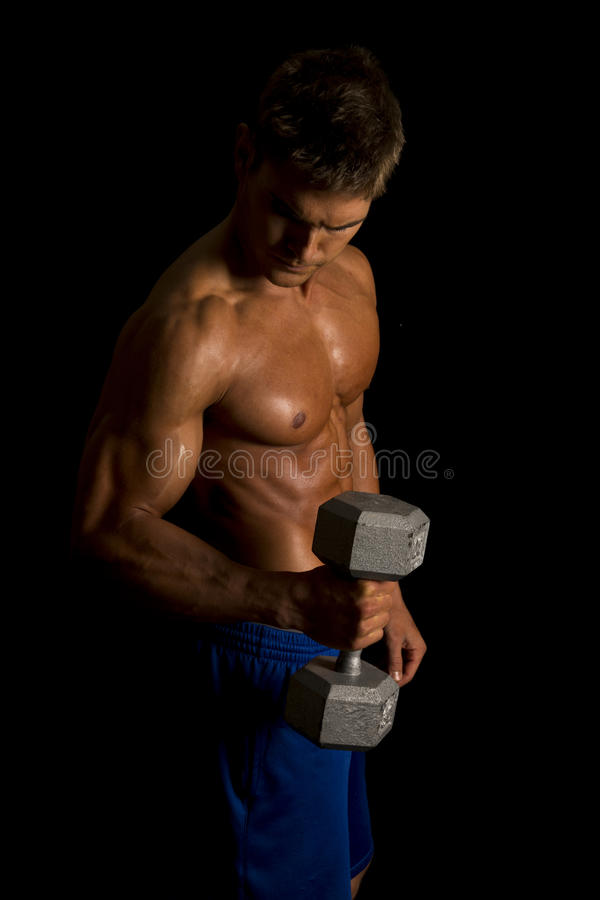 Man fitness no shirt on black hammer curl. A man on a black background doing hammer curls royalty free stock images