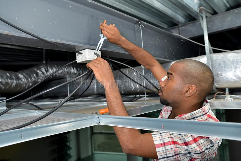 Man fitting cables into junction box. Man fitting cables into a junction box stock photos