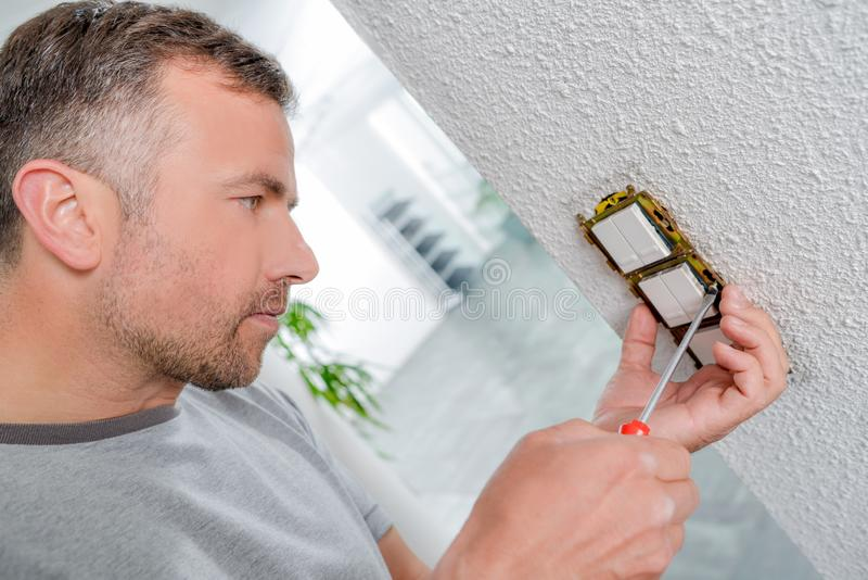 Man fitting light switches royalty free stock image