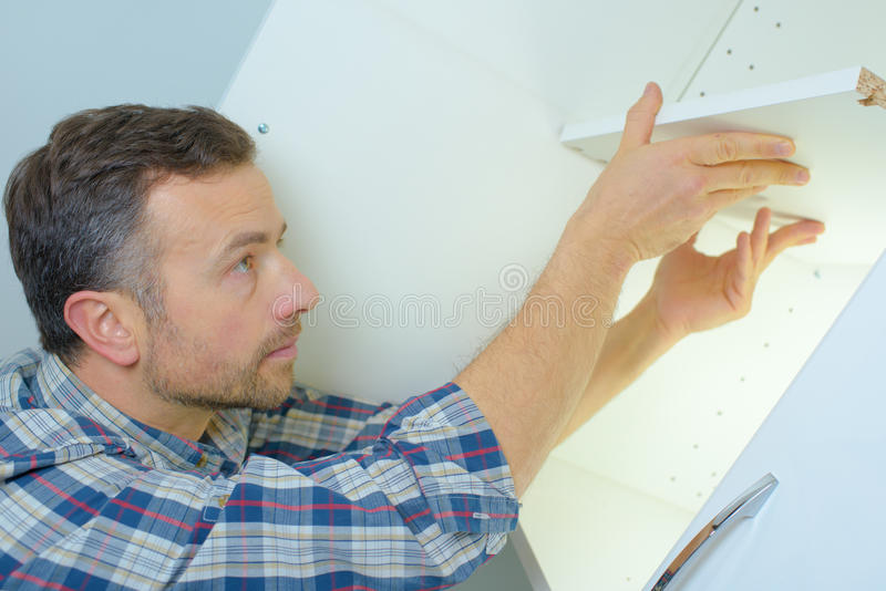 Man fitting new kitchen units. Man fitting some new kitchen units royalty free stock photography