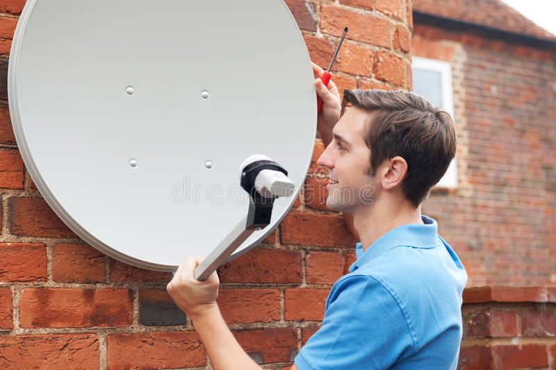 Man Fitting TV Satellite Dish To House Wall royalty free stock image