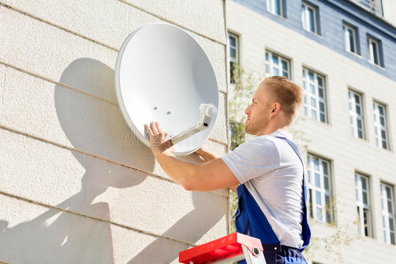 Man Fitting TV Satellite Dish. Young Man Fitting TV Satellite Dish To Wall royalty free stock images
