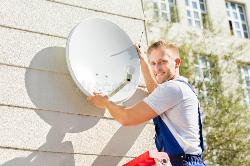 Man Fitting TV Satellite Dish. Young Man Fitting TV Satellite Dish To Wall royalty free stock image