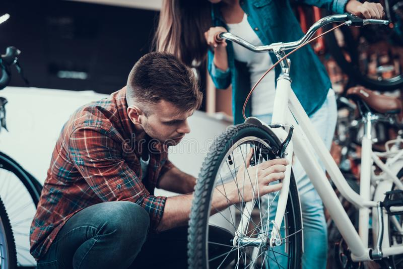 Man Fixes and Looks Attentively at Bike Brakes stock photo