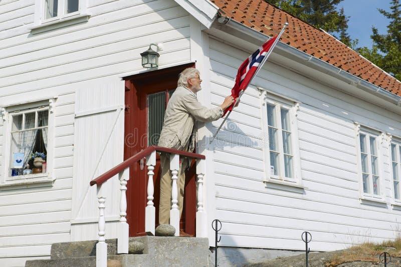 Man fixes national flag at his house in Skudeneshavn, Norway. SKUDENESHAVN, NORWAY - JUNE 05, 2010: Unidentified man fixes national flag at his house on June 05 stock photo