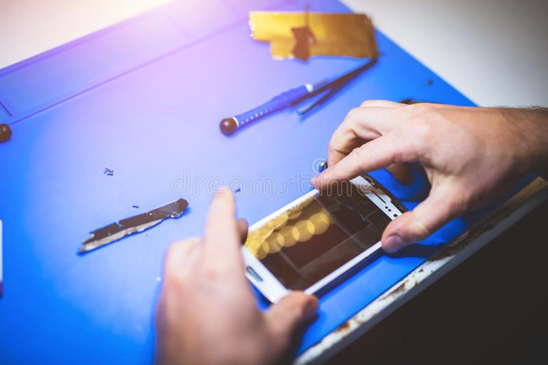 Man fixing broken mobile device. Professional reparing service. Modern devices stock image