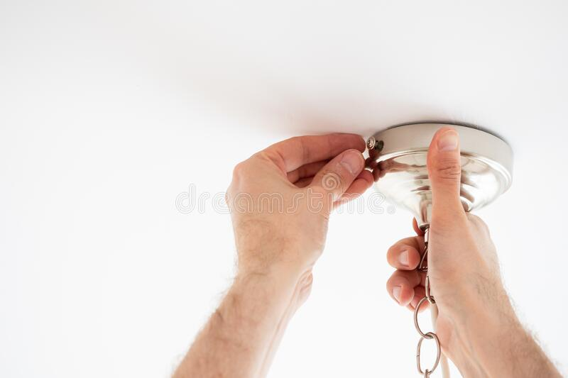 Man fixing ceiling light on white background royalty free stock image