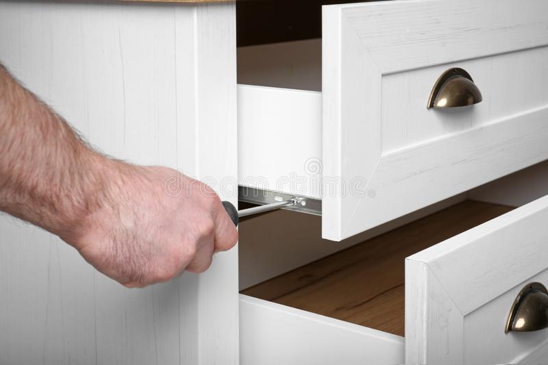 Man fixing drawer of white wardrobe with screwdriver royalty free stock photography