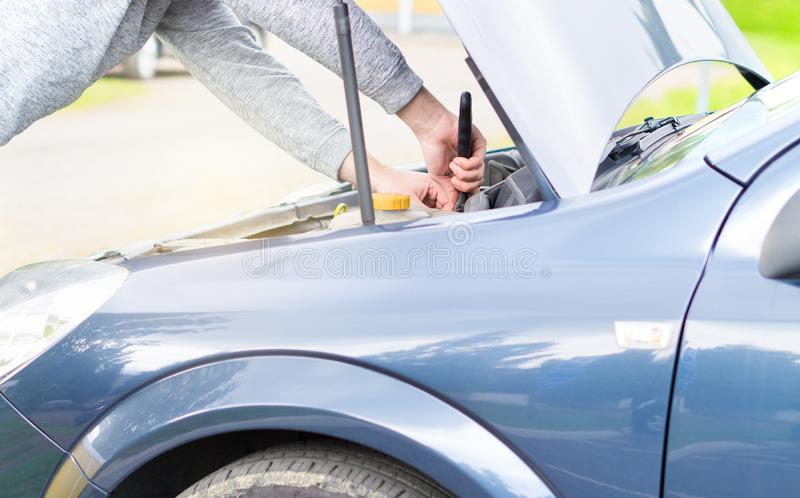 Man fixing engine under the hood with a monkey wrench. royalty free stock photography