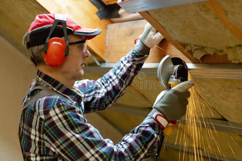 Man fixing metal frame using angle grinder on attic ceiling covered with rock wool stock images