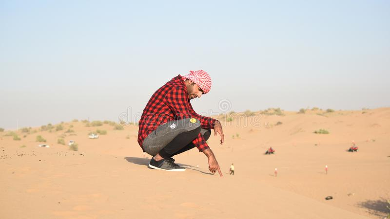 Man in Flannel Shirt Sitting on Sand royalty free stock photo