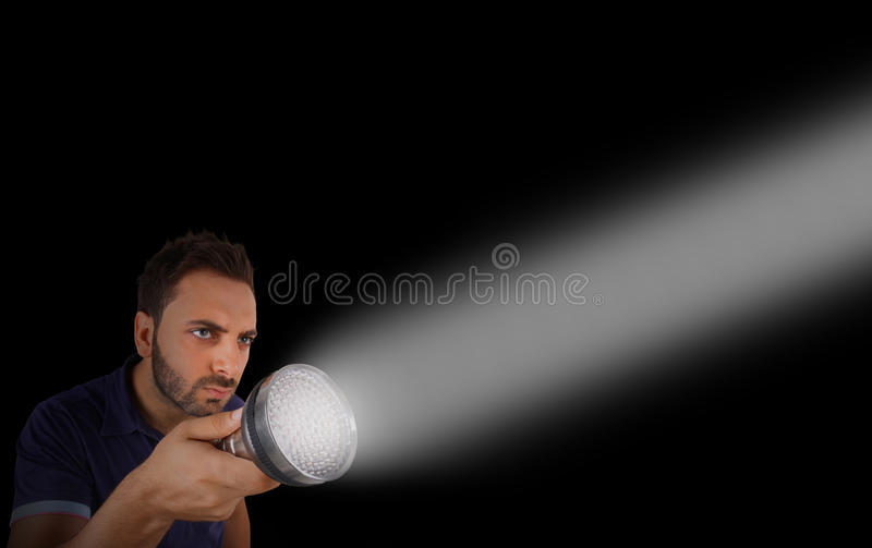 Man with a flashlight in the dark. Young man with a flashlight in the dark royalty free stock images