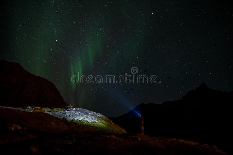Man with flashlight and northern lights on sky royalty free stock photos