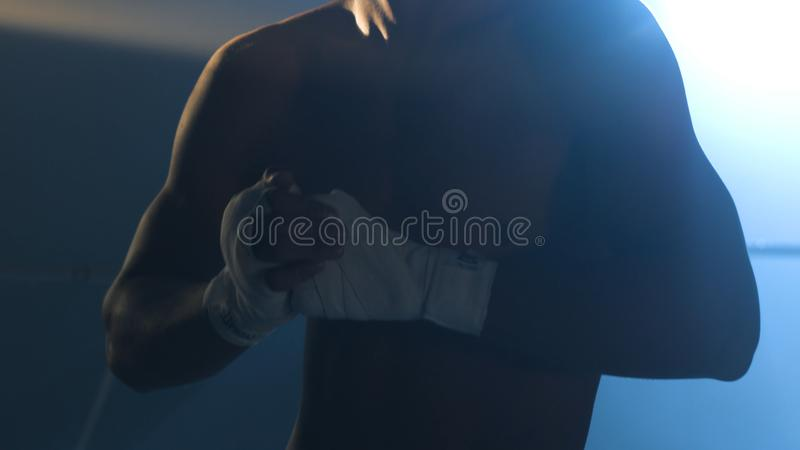 Man flexing his fists before a fight. Close-up of a young Thai boxer hands hemp ropes are wrapped before the fight or royalty free stock photos