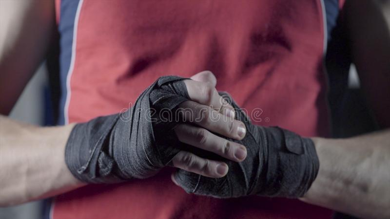 Man flexing his fists before a fight. Close-up of a young Thai boxer hands hemp ropes are wrapped before the fight or stock photos