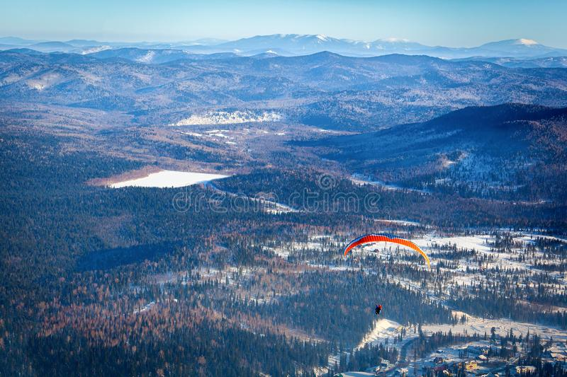 Man flies with an orange parachute. A man flies with an orange parachute, a hang-glider from the top of a snow-covered mountain in a ski resort, from above a stock photography