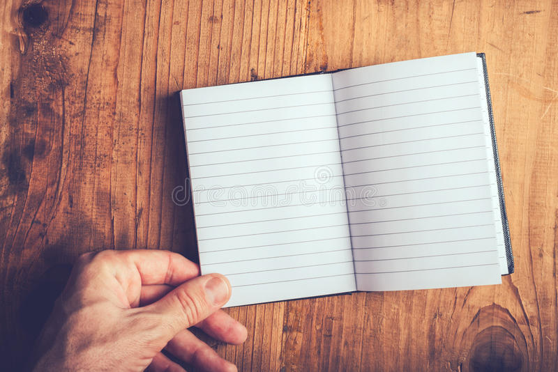 Man flipping pages of blank notebook. Top view of male hand flipping blank notebook pages, retro toned, selective focus stock photography