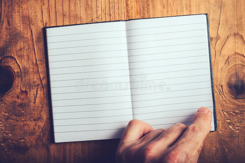 Man flipping pages of blank notebook. Top view of male hand flipping blank notebook pages, retro toned, selective focus royalty free stock image