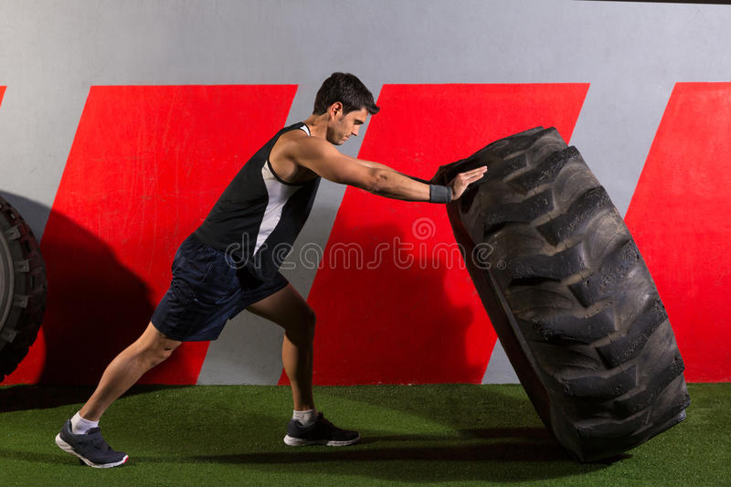 Man flipping a tractor tire workout gym exercise royalty free stock photos