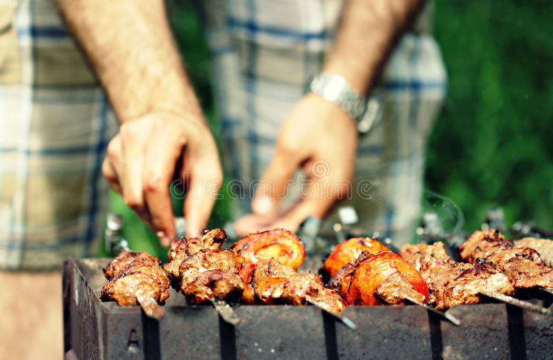 Man Flips Meat Skewers at Summer Barbecue. A man with a watch flips meat skewers at a summer barbecue. The meat is tender and flavorful royalty free stock photos