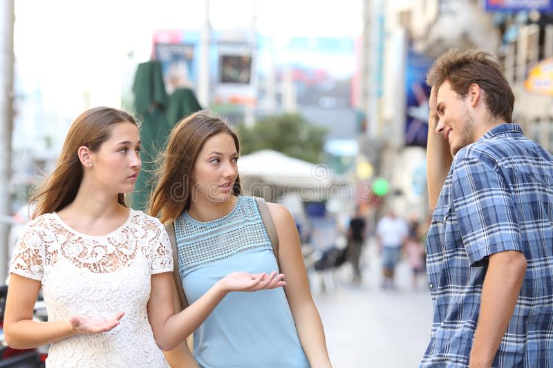 Man flirting with disappointed women in the street royalty free stock image