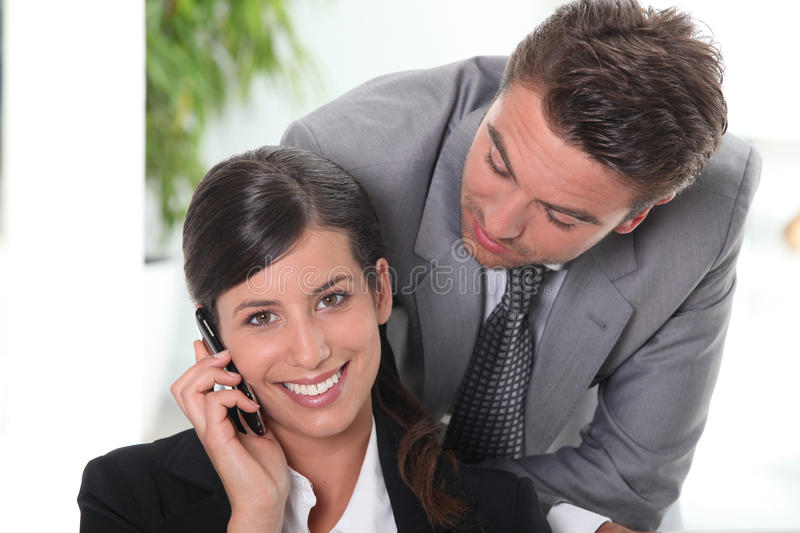 Man flirting with his colleague stock images