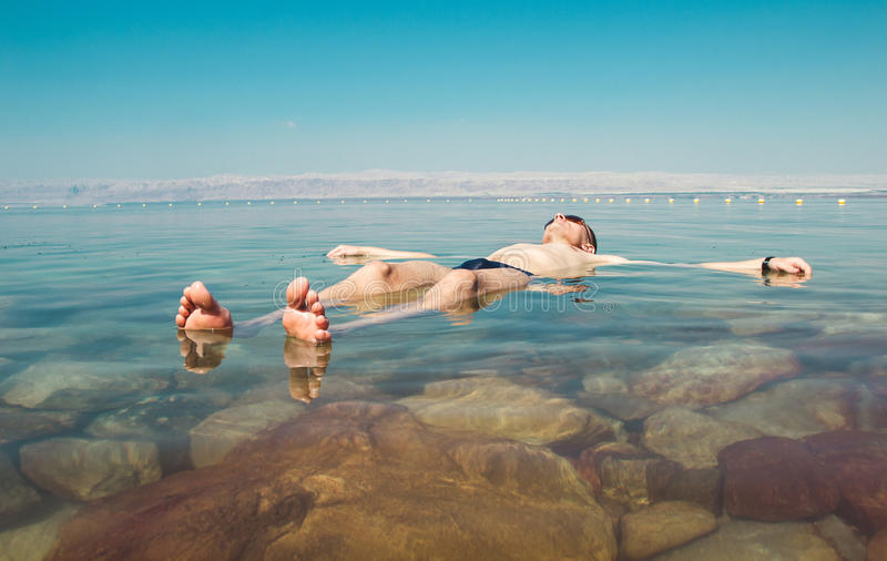 Man float meditating in water Dead Sea. Tourism recreation, healthy lifestyle concept. Copy space. Peaceful meditation stock image
