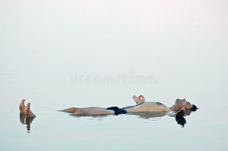 Man floating in a glassy water of dead sea royalty free stock photography