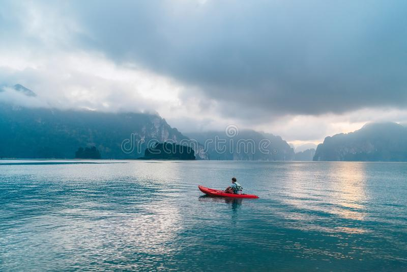 Man floating in kayak on Cheow Lan Lake in Khao Sok National Park, Thailand at early morning time royalty free stock image