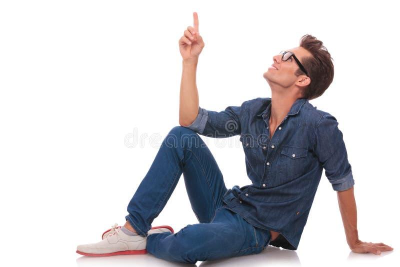 Man on floor point & looks up