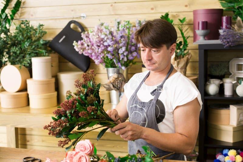 Man florist assistant in flower shop delivery make rose bouquet stock photos