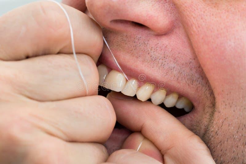Man flossing teeth stock photos