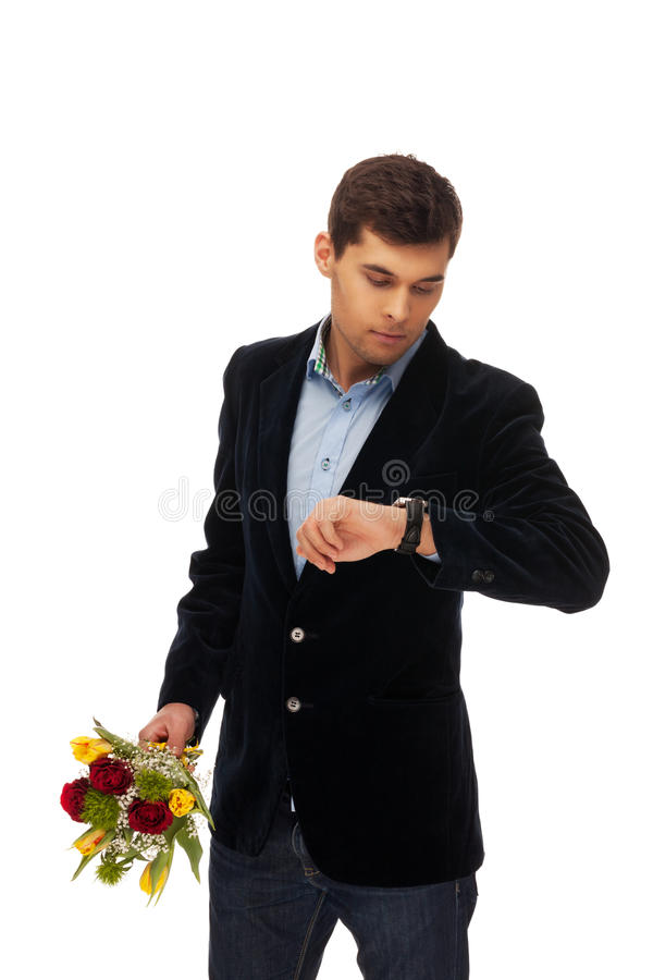 She is late. Man with flowers waiting for a girl royalty free stock photo