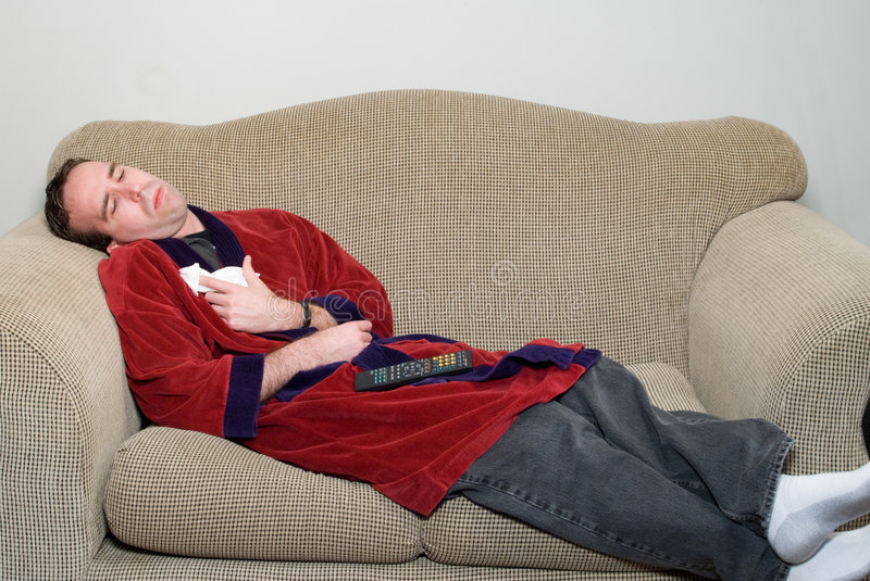 Man With The Flu. A young man laying on a sofa in his bathrobe, feeling ill because he has the flu royalty free stock images