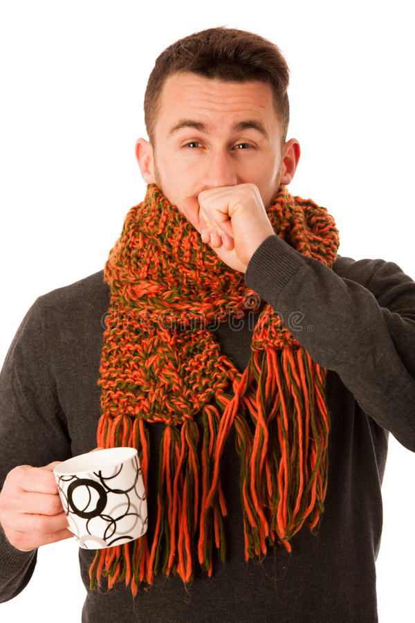 Man with flu and fever wrapped in scarf holding cup of healing t. Ea and coughing isolated over white royalty free stock image