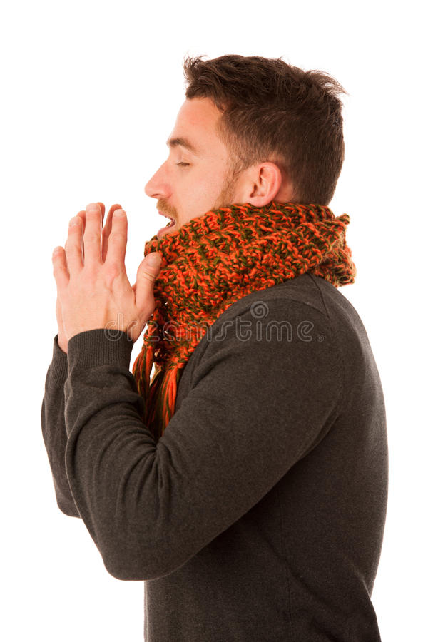 Man with flu and fever wrapped in scarf holding cup of healing t. Ea and coughing isolated over white stock photo