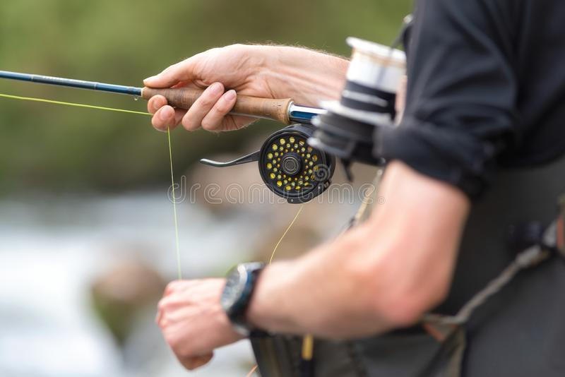 Man fly fishing with reel and rod. Sport fly fisher man close up on reel. stock photo