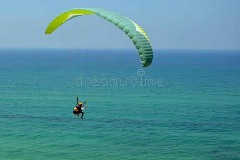 Man is flying on green paraglider in the sky above the azure sea. Balance, extreme sports, lifestyle. Mediterranean Sea Israel. Man is flying on green paraglider royalty free stock images