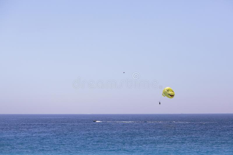 A man is flying on a parachute for a boat. Parasailing. stock photo