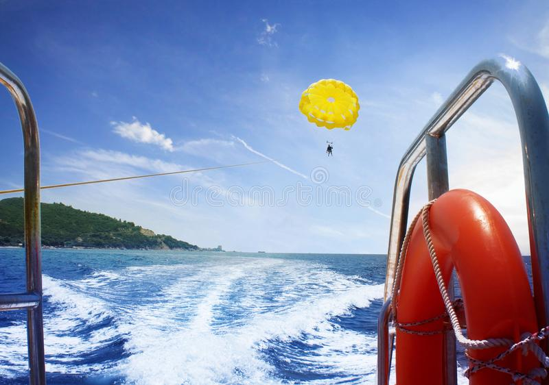 Man is flying on a paraglider on the sea from a boat stock photography