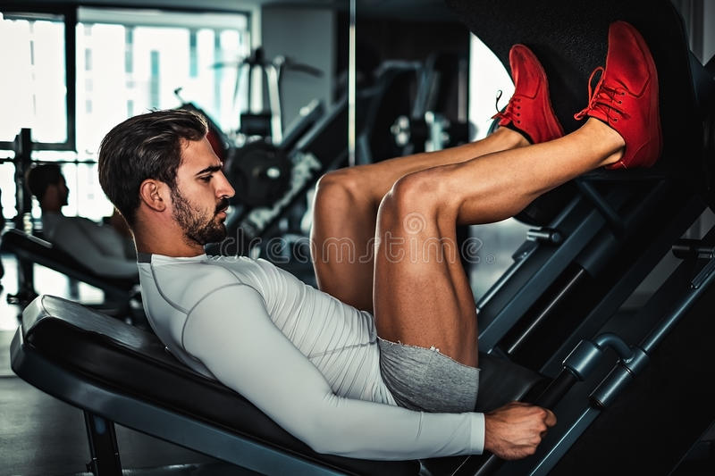 Man focused on training legs on the machine. In the gym stock image