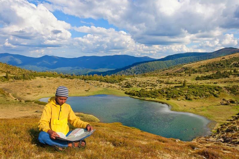 Man focuses on map near lake in Carpathian Mountains. Ukraine. Man focuses on the map near the Lake in the Carpathian Mountains in autumn. Ukraine stock photography