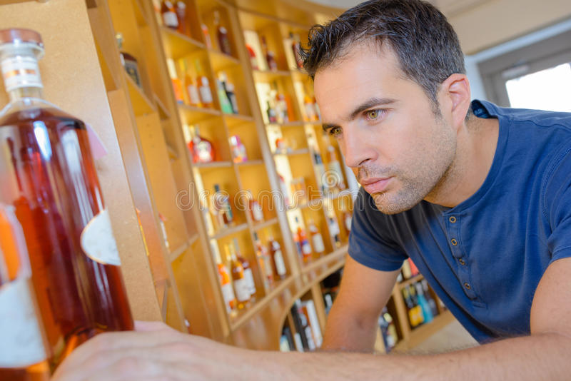 Man focusing on bottle cognac. Man focusing on bottle of cognac royalty free stock photography