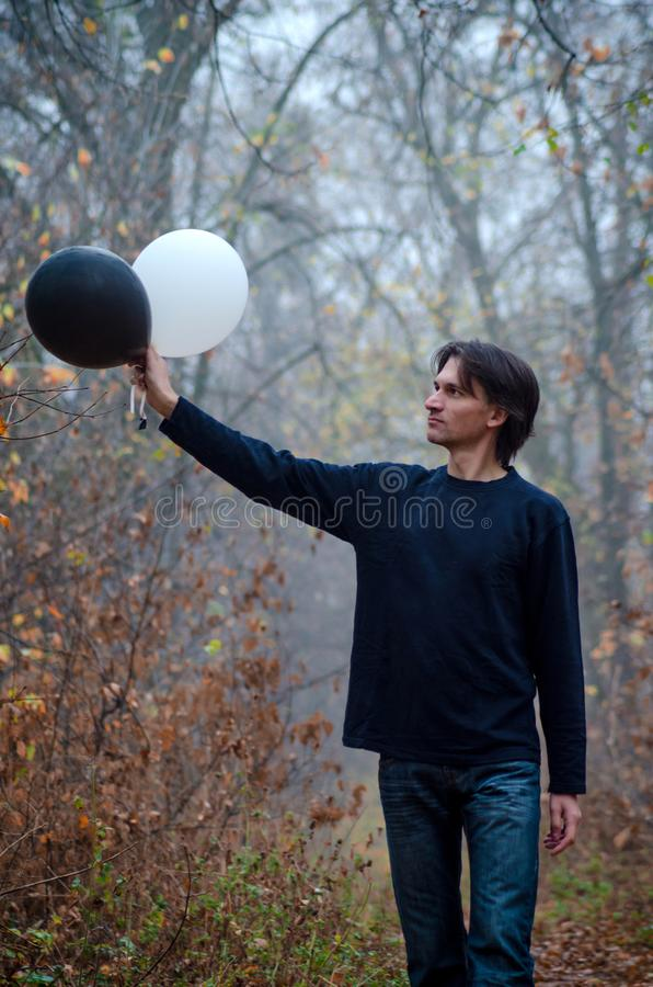 Man in foggy forest goes and looks at a black and white balloon in his hand, thinks about life, good and evil, closeup royalty free stock images