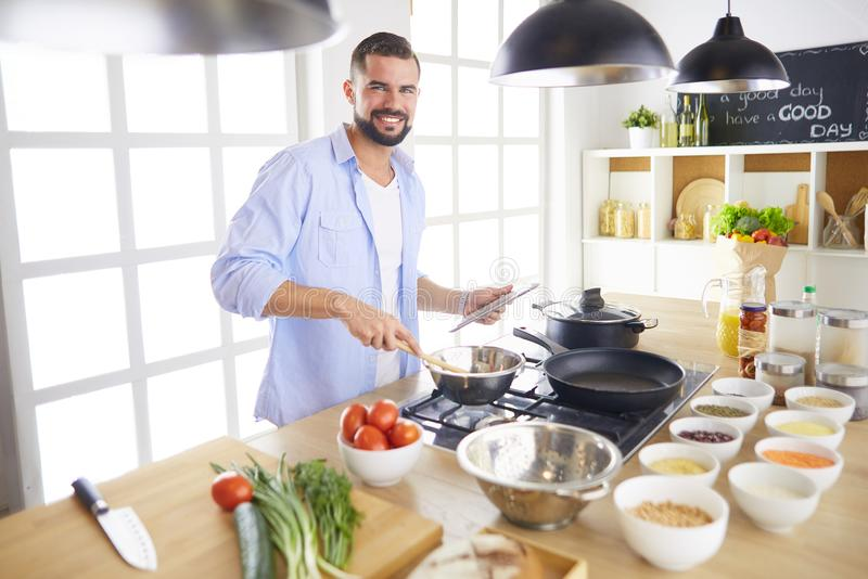 Man following recipe on digital tablet and cooking tasty and healthy food in kitchen at home royalty free stock photography