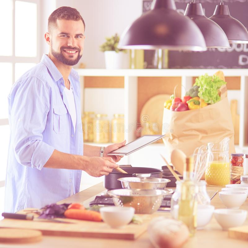 Man following recipe on digital tablet and cooking tasty and healthy food in kitchen at home.  stock photos