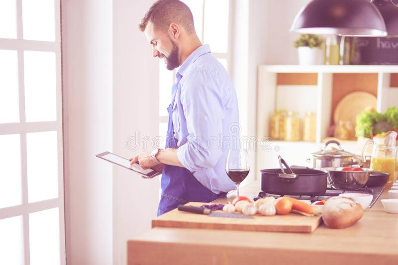 Man following recipe on digital tablet and cooking tasty and healthy food in kitchen at home.  royalty free stock image