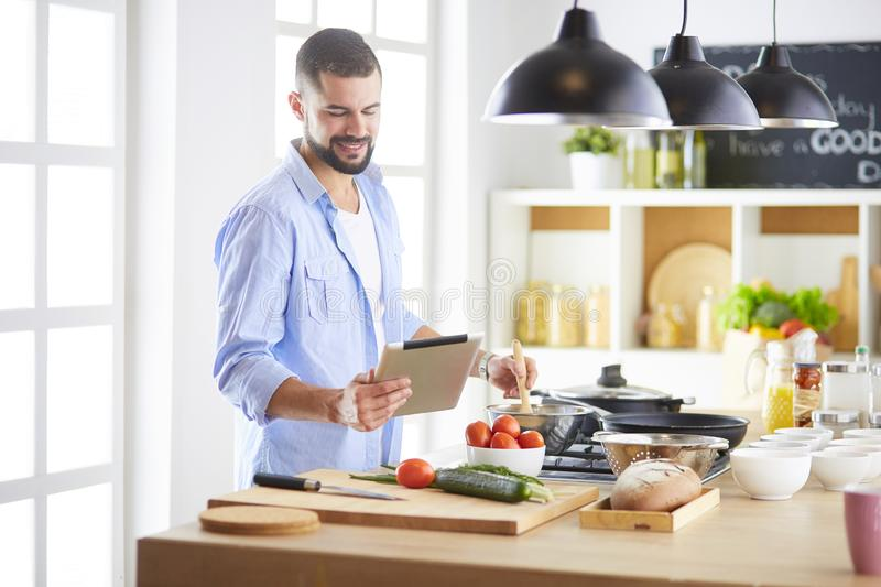 Man following recipe on digital tablet and cooking tasty and healthy food in kitchen at home stock image